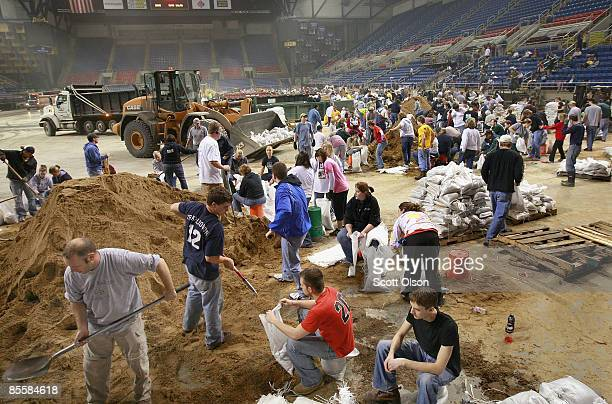 Volunteers fill sandbags during a sandbagging operation at the Fargo Dome March 24 2009 in Fargo North Dakota The city has launched a massive...
