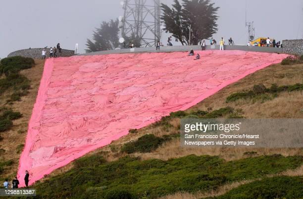Volunteers finish installing the giant pink triangle on Twin Peaks to kick off Pride weekend festivities in San Francisco, Calif. On Saturday, June...