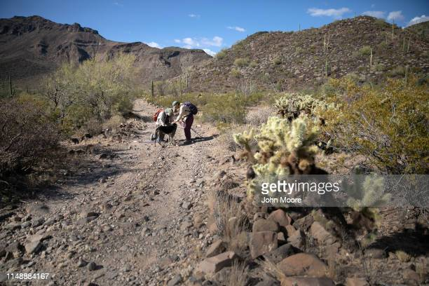 Volunteers for the humanitarian aid group No More Deaths pause while delivering water along remote immigrant trails on May 11 2019 near Ajo Arizona...