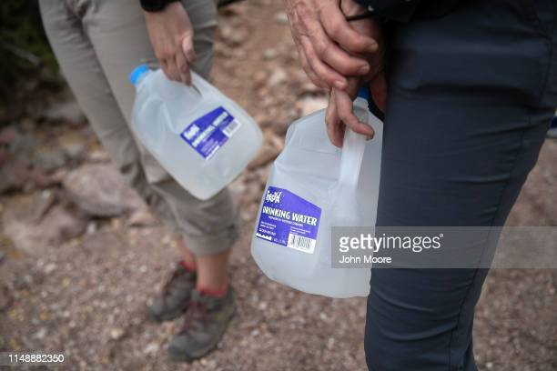 Volunteers for the humanitarian aid organization No More Deaths hold jugs of water for undocumented immigrants on May 10 2019 near Ajo Arizona The...