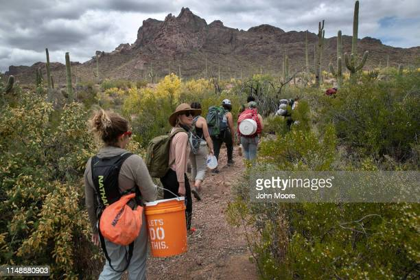 Volunteers for the humanitarian aid organization No More Deaths walk with buckets of food and jugs of water for undocumented immigrants on May 10...