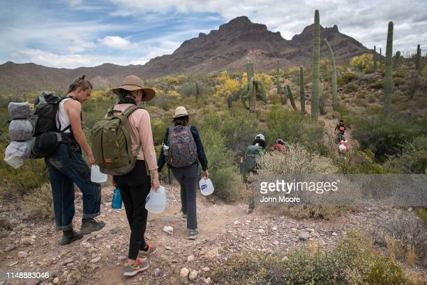 Volunteers for the humanitarian aid organization No More Deaths walk with jugs of water for undocumented immigrants on May 10 2019 near Ajo Arizona...