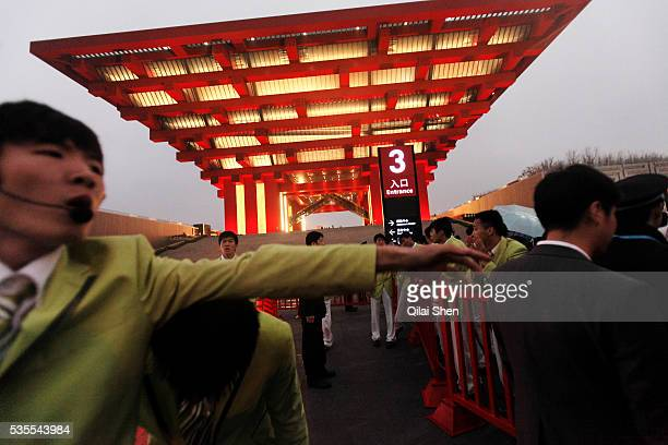 Volunteers form a human chain as visitors wait in line to enter the China Pavilion during the first day of the trail run for the 2010 World Expo in...