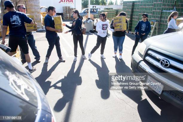 Volunteers form a supply chain as they load Lemonades into vehicles during the Girl Scout Cookie Mega Drop at the Anaheim Business Complex in Anaheim...