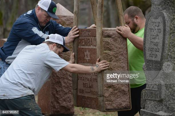 Volunteers from a local monument company help to reset vandalized headstones at Chesed Shel Emeth Cemetery on February 22 2017 in University City...