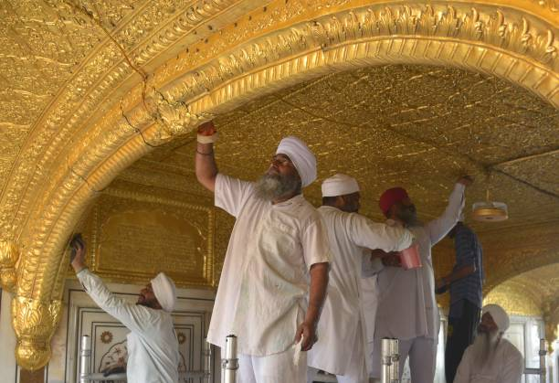 Volunteers from Birmingham`s Guru Nanak Nishkam Sewak Jatha in Britain clean the gold plating at the Sikh Golden Temple in Amritsar on March 18 2017..