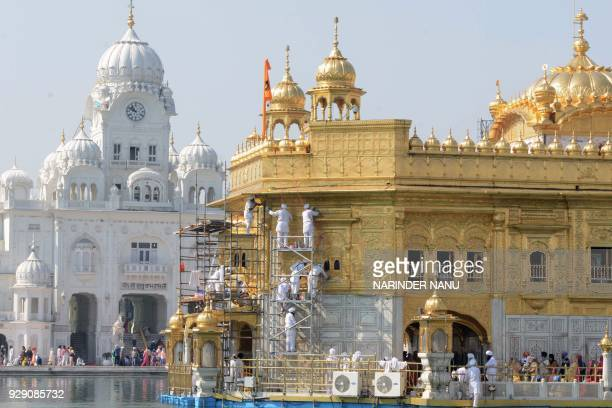 TOPSHOT Volunteers from Birmingham's Guru Nanak Nishkam Sewak Jatha in Britain clean the gold plating of the Golden Temple Sikh Shrine in Amritsar on...