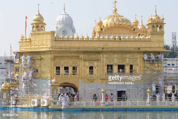 Volunteers from Birmingham's Guru Nanak Nishkam Sewak Jatha in Britain clean the gold plating of the Golden Temple Sikh Shrine in Amritsar on March 8...
