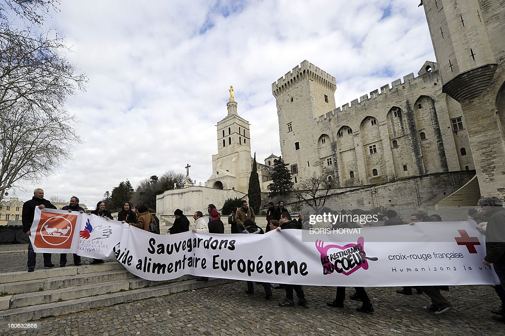 Volunteers from food aid associations such as Banques Alimentaires, Croix-Rouge, Restos du Coeur and Secours Populaire, hold a banner reading in French 'Save european food aid' on February 4, 2013 ...