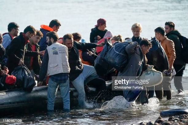 Volunteers from Light House Relief help migrants land on a beach after making the crossing from Turkey to the Greek island of Lesbos on October 10...