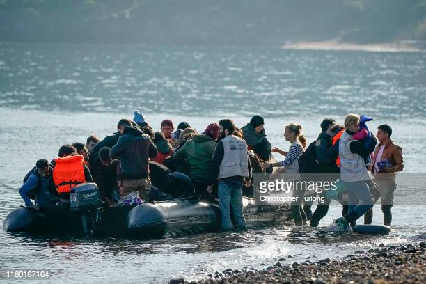 Volunteers from Light House Relief help migrants land on a beach after making the crossing from Turkey to the Greek island of Lesbos on October 10,...