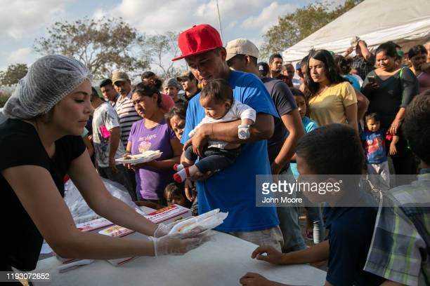 Volunteers from Reynosa Mexico serve a meal to asylum seekers at an immigrant camp on December 08 2019 in the border town of Matamoros Mexico More...