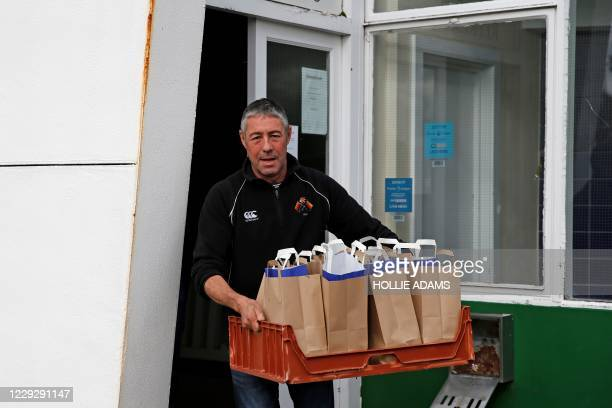 Volunteers from Richmond Rugby, load bags of meals into a car before delivering them to local school children in Twickenham, south west London, on...