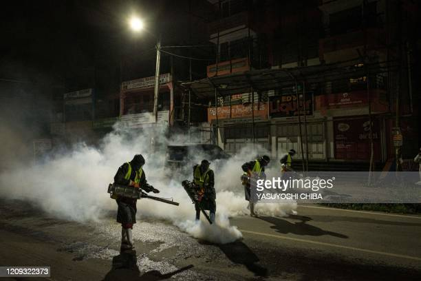 Volunteers from Sonko Rescue Team an NGO privately funded by Nairobi Governor Mike Sonko fumigate a street to curb the spread of COVID19 during a...