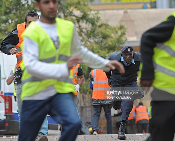 Volunteers from the asiancommunity and a police officer run for cover on September 23 2013 after hearing a volley of gunshots at the scene of a...