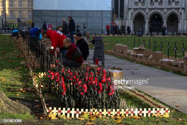Volunteers from the British Legion are seen planting crosses during the preparations Volunteers from the British Legion prepare the Field of...