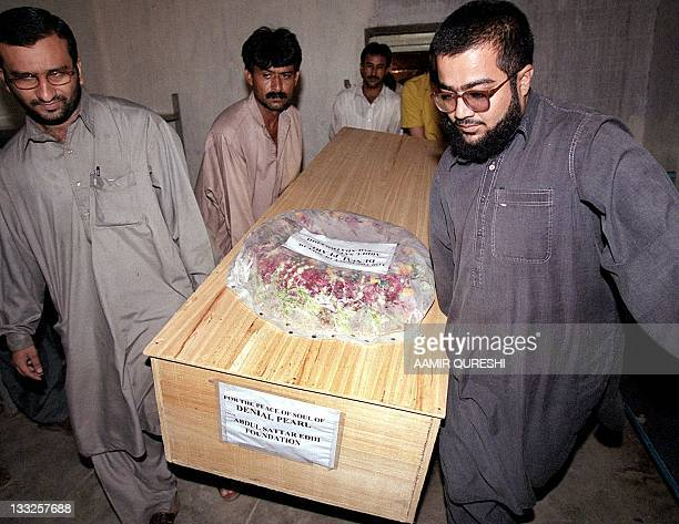 Volunteers from the Edhi Welfare Trust carry the coffin of US reporter Daniel Pearl from a mortuary in Karachi, 07 August 2002. An armed police...
