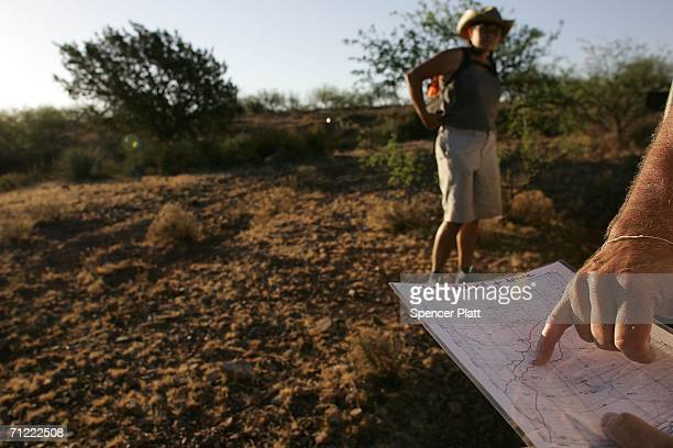 Volunteers from the humanitarian group No More Deaths check a map on a trail used by migrants entering the US illegally from Mexico June 16 2006 in...