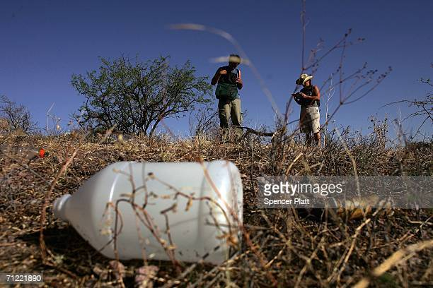 Volunteers from the humanitarian group No More Deaths examine items found on the ground on a trail used by migrants illegally entering the US from...