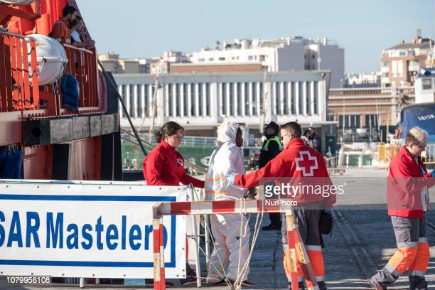 Volunteers from the Red Ross help a woman to disembark on January 9 Malaga Southern Spain