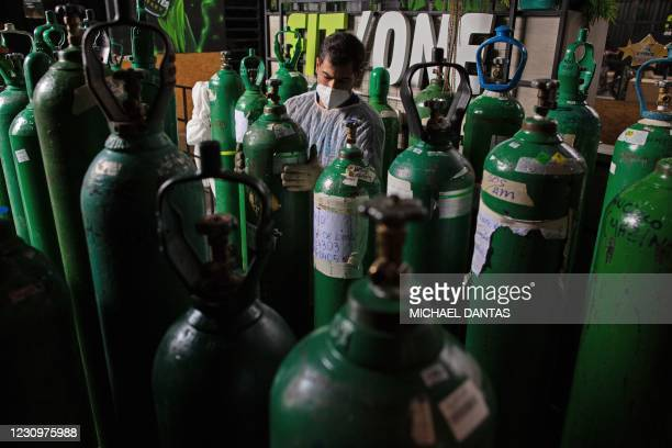 Volunteers from the SOS medical emergency services refill oxygen tanks for free, in Manaus, Brazil on January 30, 2021. - As a new pandemic wave hits...