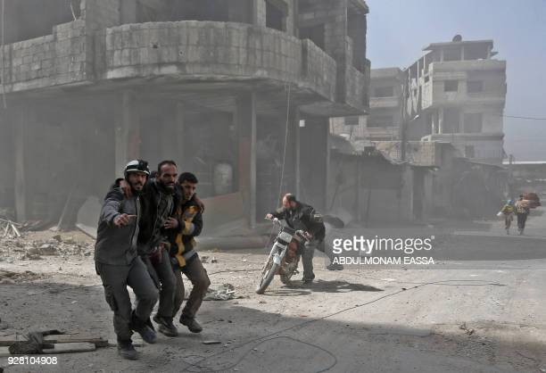 TOPSHOT Volunteers from the Syrian civil defence help a man in Hamouria during Syrian government shelling on rebelheld areas in the Eastern Ghouta...