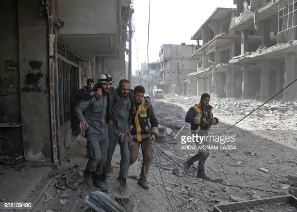 Volunteers from the Syrian civil defence help a man in Hamouria during Syrian government shelling on rebelheld areas in the Eastern Ghouta region on...