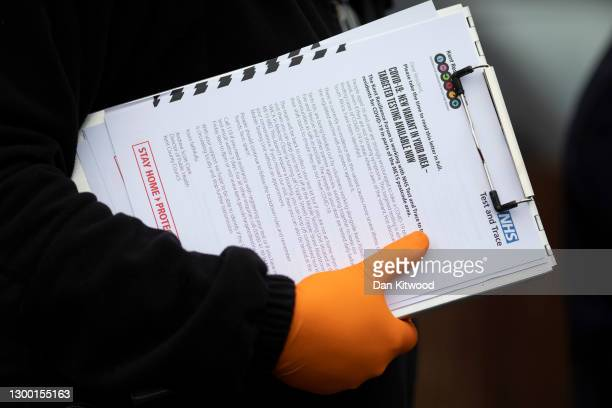 Volunteers from various emergency services and council members go door-to-door to distribute Covid-19 tests to residents homes on February 03, 2021...