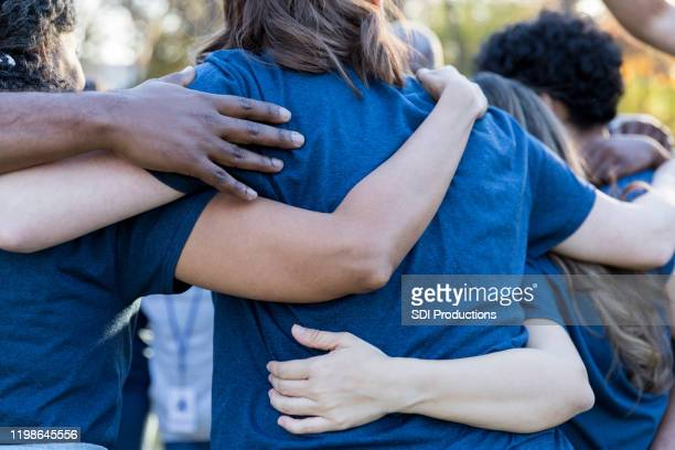 volunteers gather together during event - arm around stock pictures, royalty-free photos & images