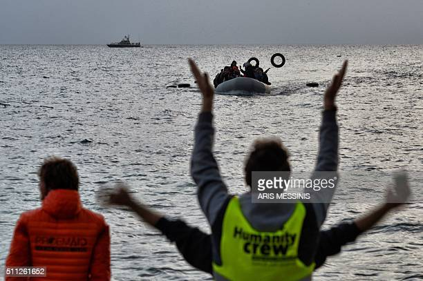 Volunteers gesture to guide refugees and migrants on a dinghy as they approach Mytilene on the northern island of Lesbos after crossing the Aegean...