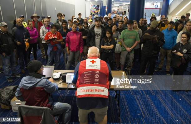 Volunteers get a briefing at the George Brown Convention Center that has been turned into a shelter run by the American Red Cross to house victims of...