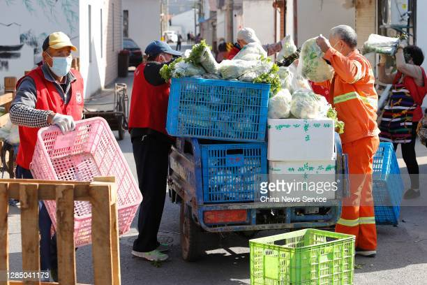 Volunteers give out vegetables to villagers at Yingqian Village after a new confirmed case of COVID-19 was reported on November 10, 2020 in Shanghai,...