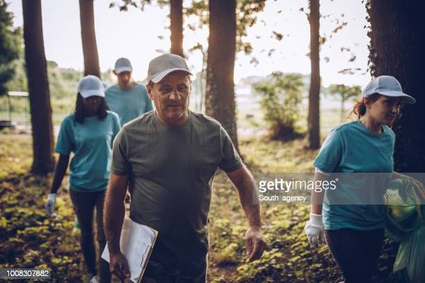 volunteers going cleaning together - environmentalist stock pictures, royalty-free photos & images
