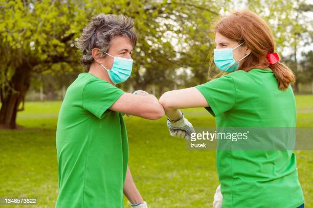 volunteers greeting with elbow bump in covid-19 - izusek stock pictures, royalty-free photos & images