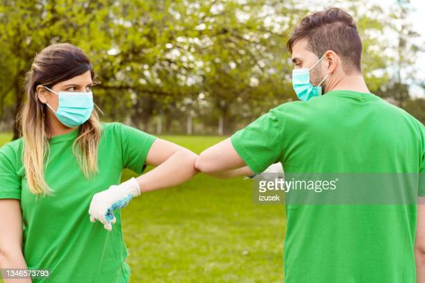 volunteers greeting with elbow bump in park - izusek stock pictures, royalty-free photos & images