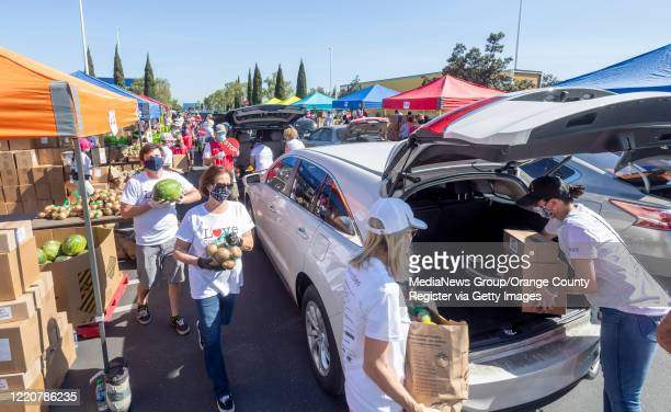 Volunteers hand out boxes of food during a drive-thru emergency food distribution in the parking lot of IKEA in Costa Mesa, CA on Thursday, April 23,...
