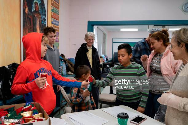 Volunteers hand out Christmas stockings with candy to Central American migrants in a shelter set up by the Immaculate Heart of Mary Catholic Church...