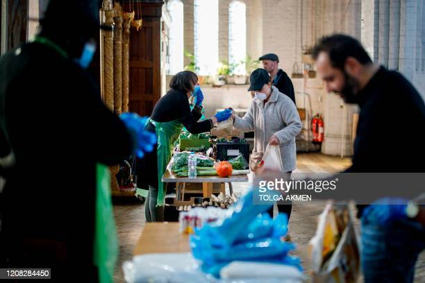 Volunteers hand out food to peopleinneed at a popup shop serving as food bank at St Margaret's Church in Leytonstone amidst the novel coronavirus...