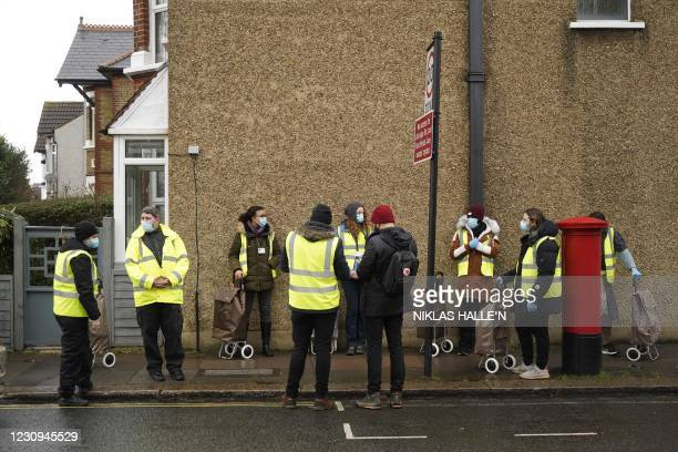 Volunteers hand-deliver Covid-19 test kits to homes in Ealing, west London, on February 3, 2021 as part of an additional testing drive in areas where...