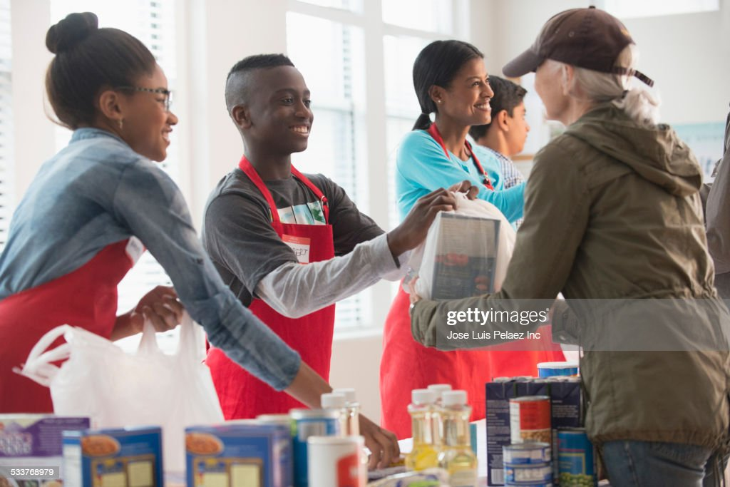 Volunteers handing out food at food drive : Foto stock