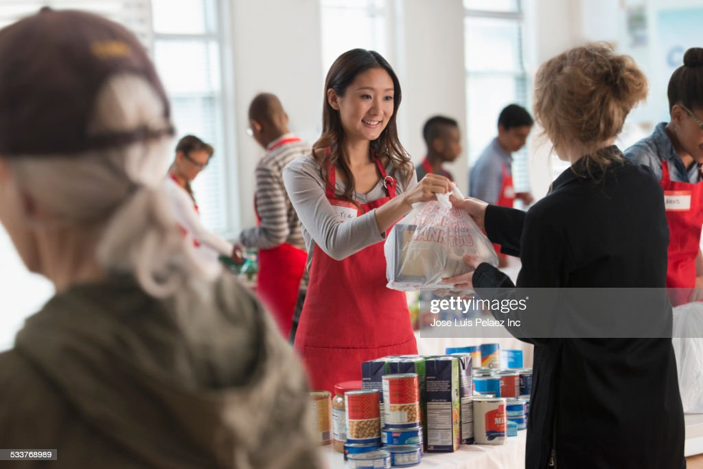 Volunteers handing out food at food drive : Stock Photo