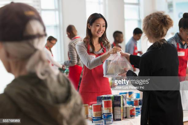 volunteers handing out food at food drive - charity and relief work stock pictures, royalty-free photos & images