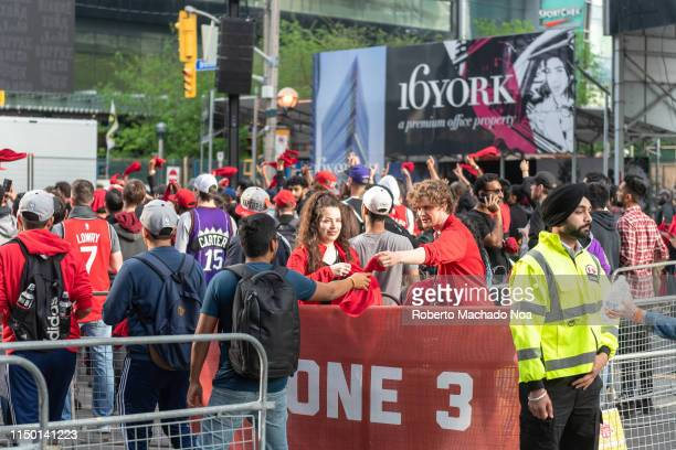 Volunteers handing out red cloths to fans entering the exterior fan areas in the Bremner Boulevard NBA playoffs fever in the Canadian cityIt is the...