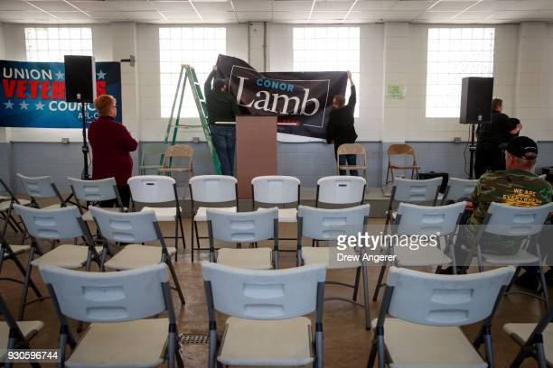 Volunteers hang a banner before the start of a rally for Conor Lamb Democratic Congressional candidate for Pennsylvania's 18th district at the Greene...