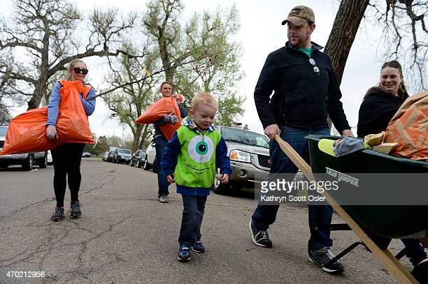 Volunteers Hannah Meyer left and her brother Logan help carry two trees for Sonja right and Andrew Hausmann and their son Douglas to their car Denver...