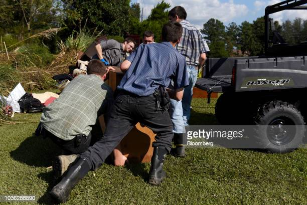 Volunteers help a family clear their belongings from a flooded home after Hurricane Florence hit in Chinquapin, North Carolina, U.S., on Wednesday,...