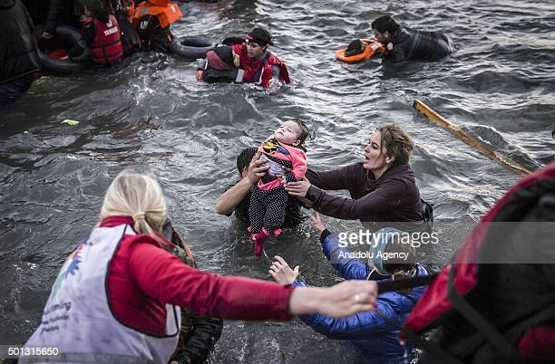 Volunteers help a refugee man and baby as refugees hoping to cross into Europe arrive on the shore of Greeces Lesbos Island after crossing the Aegean...