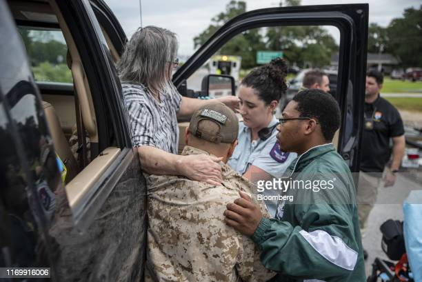 Volunteers help an injured woman out of a truck following Tropical Storm Imelda in Fannett Texas US on Friday Sept 20 2019 The remnants of Tropical...