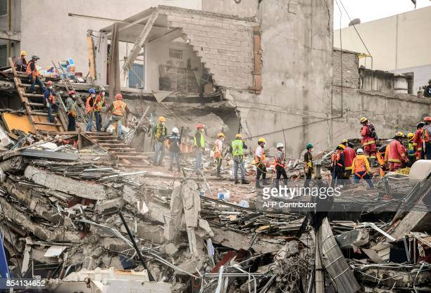 Volunteers help as rescuers still search for victims in a building toppled by a magnitude 71 quake that struck central Mexico a week ago in Mexico...