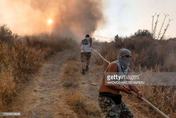 Volunteers help carry a firehose in an effort to contain a fire near the Kotsiatis area, on the outskirts of Cyprus' capital Nicosia on July 4, 2021....
